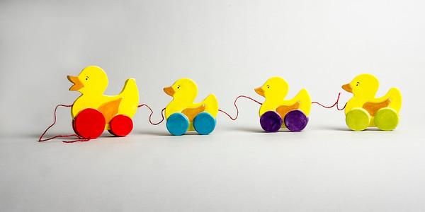 "Toy ducks pulley, white earthen ware, hand built, under glaze, yarn: h. 5.5"", w  26.5"",d 1.5"""
