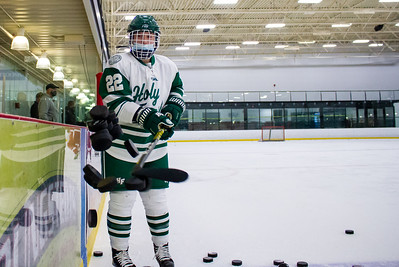 Olivia Paidosh sweeps a pile of pucks off the bench to start warmups before a game against Benilde - St. Margaret's on February 2, 2021.