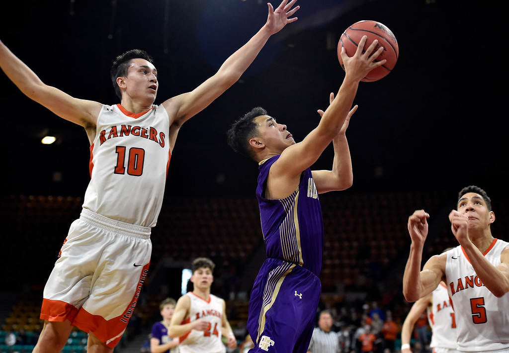 . DENVER, CO - MARCH 8, 2019: Holy Family High School\'s Dominic Nellis goes for a layup under Noah Baca during a CHSAA 4A Final Four playoff game against Lewis Palmer on Friday at the Denver Coliseum. Holy Family lost the game. More photos: BoCoPreps.com (Photo by Jeremy Papasso/Staff Photographer)