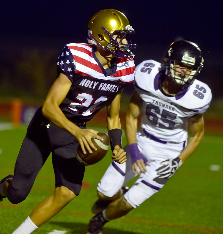 . BROOMFIELD CO - SEPTEMBER 14 2018 Holy Family High School\'s Calahan Carter scrambles away from Discovery Canyon High\'s Eli Scott during their game in Broomfield on Friday September 14, 2018. More photos bocopreps.com  (Photo by Paul Aiken/Staff Photographer)