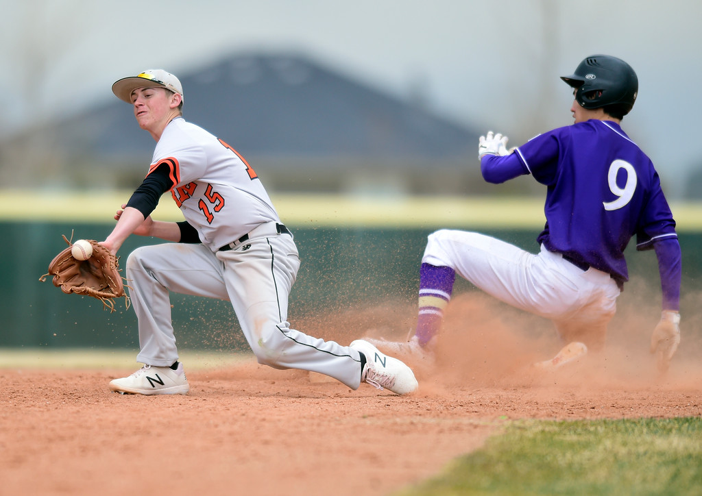 . Erie High School\'s Trevor Ball misses the tag on Zach Becker at second base during a game against Holy Family on Thursday in Broomfield. More photos: BoCoPreps.com Jeremy Papasso/ Staff Photographer 03/15/2018