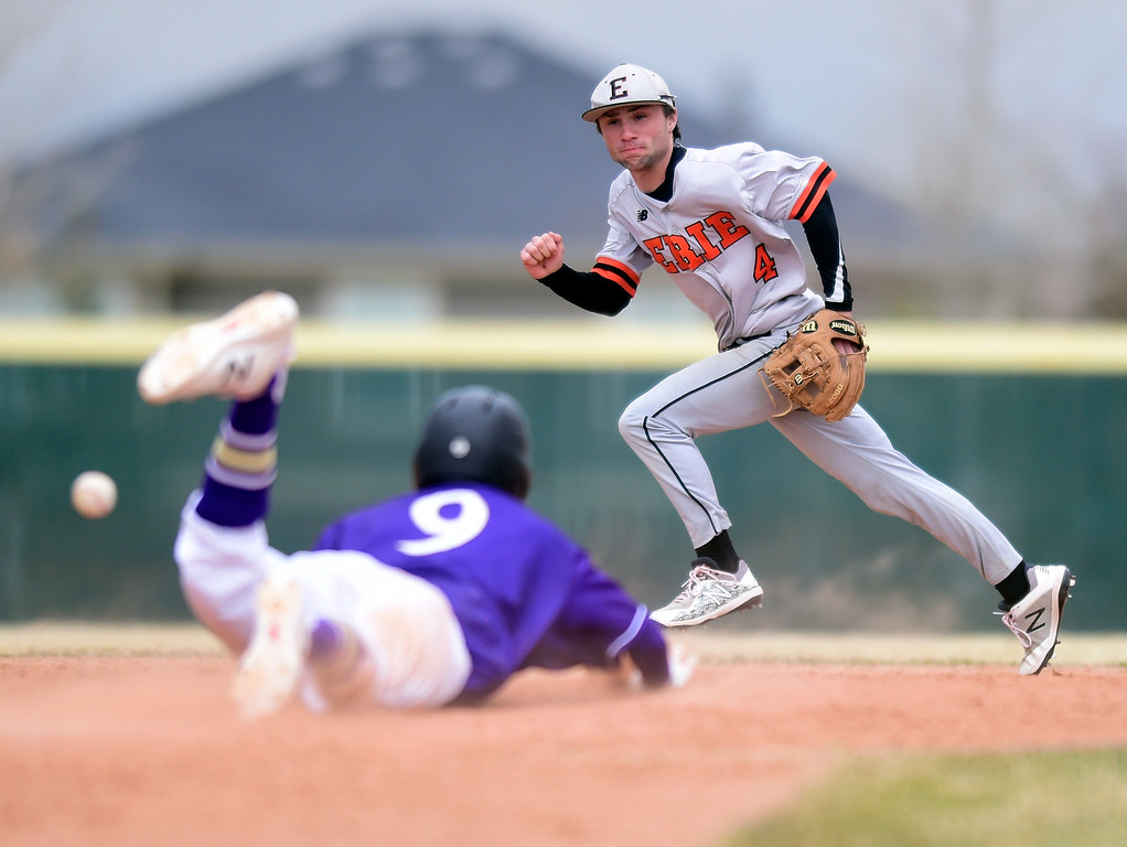. Erie High School\'s Matt Kelly chases a bad throw in an attempt to pick off Zach Becker, No. 9, during a game against Holy Family on Thursday in Broomfield. More photos: BoCoPreps.com Jeremy Papasso/ Staff Photographer 03/15/2018