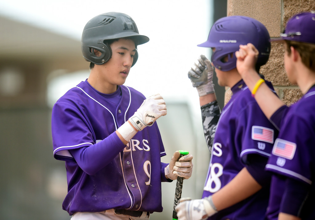 . Holy Family High School\'s Zach Becker, left, is congratulated on scoring a run by teammates during a game against Erie on Thursday in Broomfield. More photos: BoCoPreps.com Jeremy Papasso/ Staff Photographer 03/15/2018