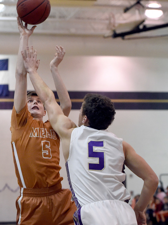 . Mead High School\'s Michael Ward takes a shot over Joe Golter during a game against Holy Family on Tuesday in Broomfield. More photos: www.BoCoPreps.com Jeremy Papasso/ Staff Photographer/ Feb. 14, 2017