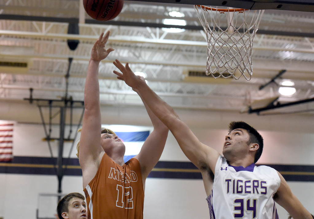 . Mead High School\'s Derek Edwards takes a shot over Cameron Miller during a game against Holy Family on Tuesday in Broomfield. More photos: www.BoCoPreps.com Jeremy Papasso/ Staff Photographer/ Feb. 14, 2017