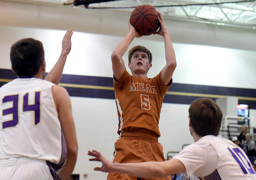 . Mead High School\'s Michael Ward takes a shot over a swarm of defenders during a game against Holy Family on Tuesday in Broomfield. More photos: www.BoCoPreps.com Jeremy Papasso/ Staff Photographer/ Feb. 14, 2017