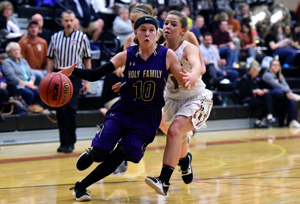 . Holy Family High School\'s Kaitlyn McKenzie dribbles past Alanna Hernandez during a game against Mead on Tuesday in Mead. More photos: BoCoPreps.com Jeremy Papasso/ Staff Photographer 02/13/2018