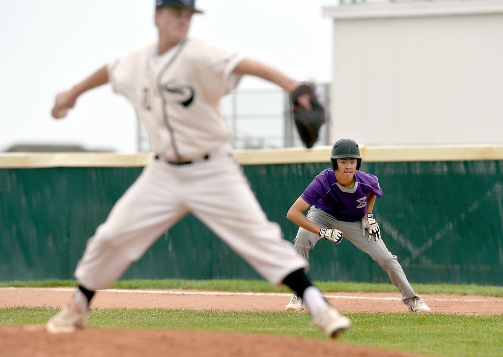 . Holy Family\'s Luke Knudson gets a lead at first base during a Boulder NIT game against the Slammers Fiscus on Thursday at Holy Family High School in Broomfield. More photos: BoCoPreps.com Jeremy Papasso/ Staff Photographer 07/12/2018