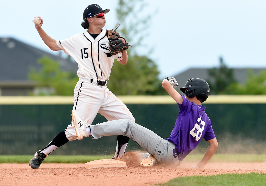 . Holy Family\'s Luke Knudson is forced out at second base by Nate Schraeder during a double play during a Boulder NIT game against the Slammers Fiscus on Thursday at Holy Family High School in Broomfield. More photos: BoCoPreps.com Jeremy Papasso/ Staff Photographer 07/12/2018