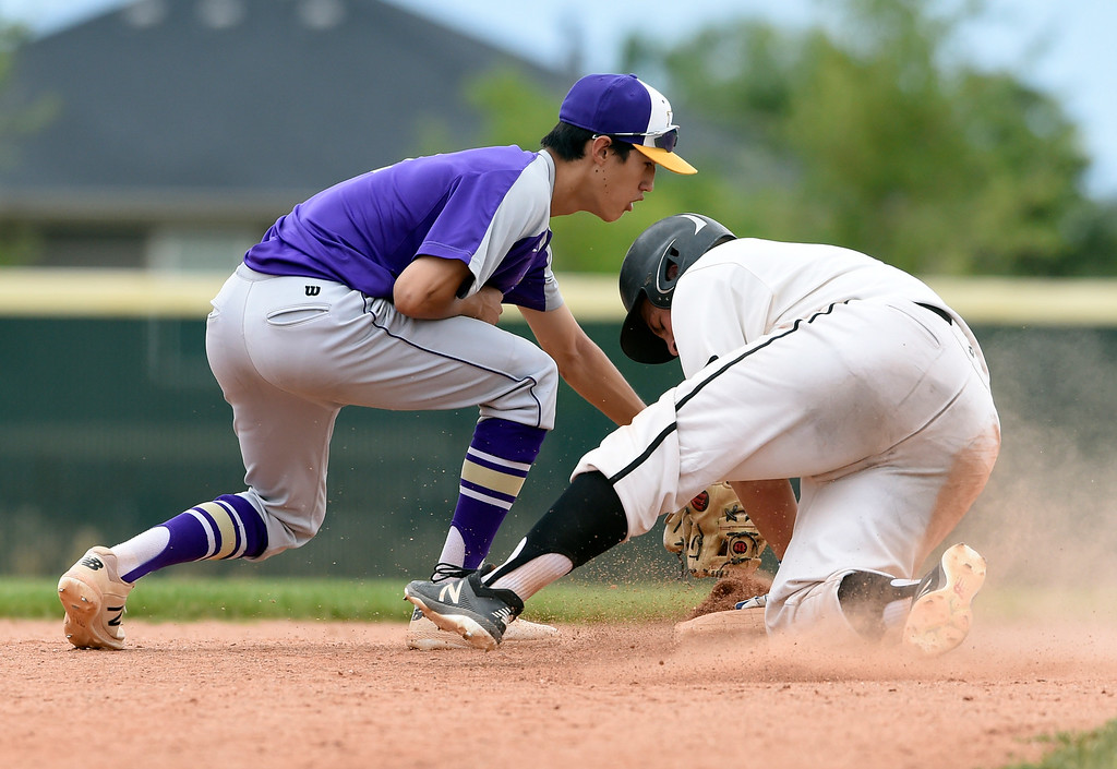 . Holy Family\'s Zack Becker misses the tag on Jake Simmons at second base during a Boulder NIT game against the Slammers Fiscus on Thursday at Holy Family High School in Broomfield. More photos: BoCoPreps.com Jeremy Papasso/ Staff Photographer 07/12/2018