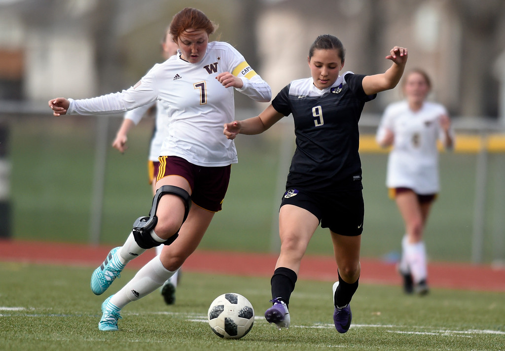 . Holy Family High School\'s Jaelen Giron moves the ball past Adalyn Vergara during a game against Windsor on Monday in Windsor. More photos: BoCoPreps.com Jeremy Papasso/ Staff Photographer 04/16/2018