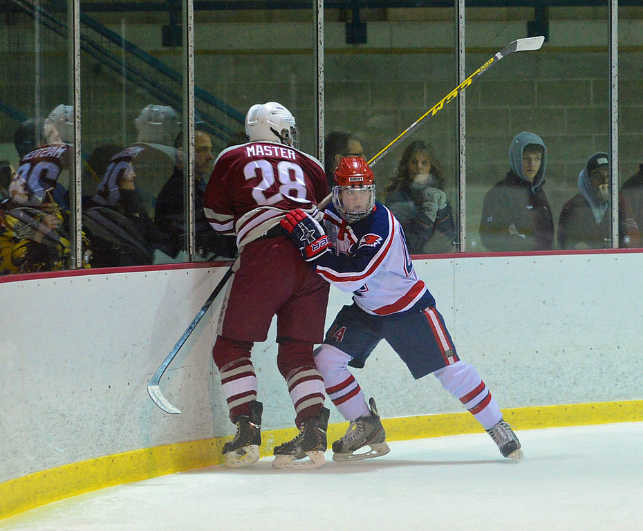 . Colin Costello (44) slams Nathan Masters (28) into the boards.