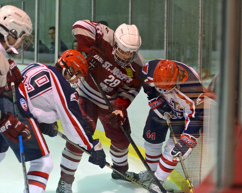 . Colin Costello (44) and Byron Hartley (49) battle Nathan Master (28) on the boards.