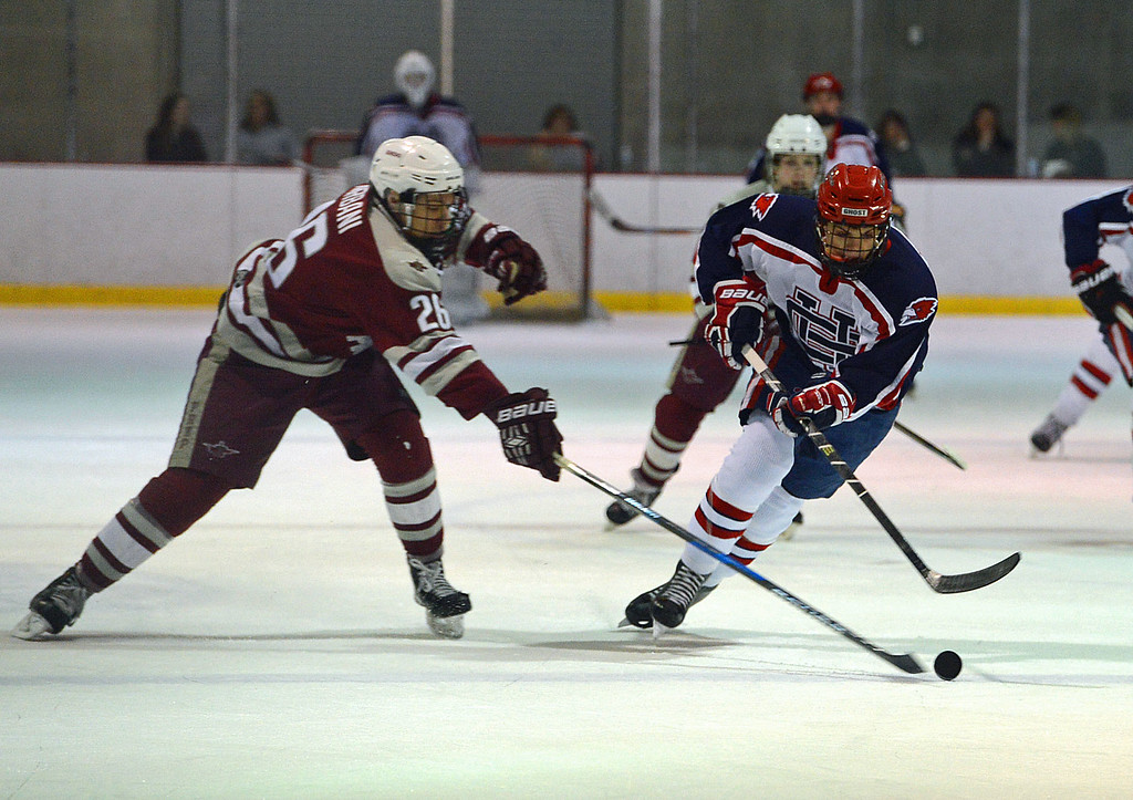 . Zach Babst (20) races Nick Urbani (26) to the puck.