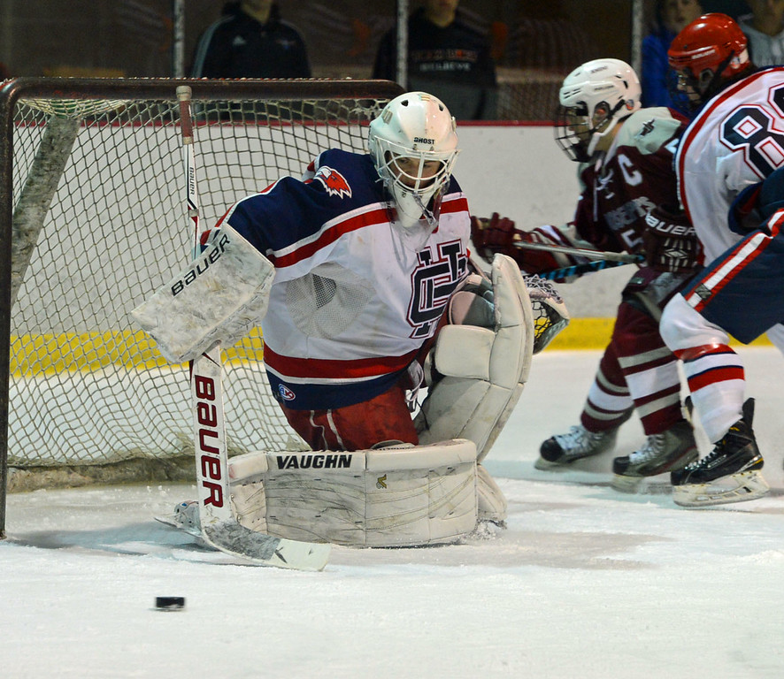 . Goalie Tristan Devine (30) gets set to pounce on the puck.