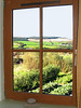View through a bedroom window of the kitchen garden and the Arran hills