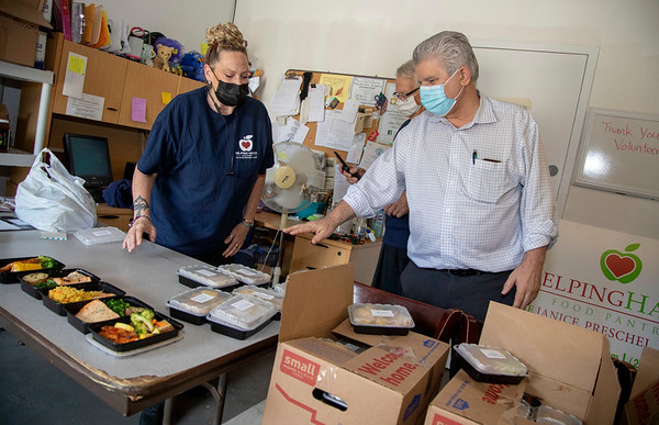 Karen McEvoy and Mike Koscuiszka (white hair), volunteers at Helping Hands Food Pantry in Teaneck, accept donations from Nick Lulani (light dress shirt), owner, of Amarone's Ristorante in Teaneck. 06/15/2021 Photo by Jeff Rhode/Holy Name Medical Center