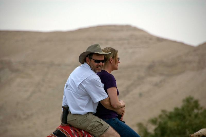 Joe holding onto Sylvia while riding the camel.