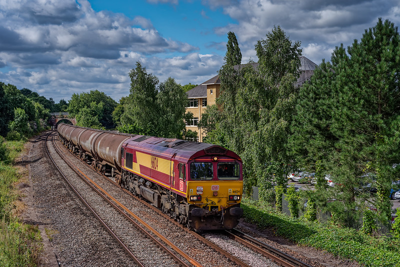 66124 passes the site of the former Peasmarsh Junction with 6Y32, the 08:24 Fawley - Holybourne empty tanks, on 8th August 2016. The loco was carrying a headboard, see next photo for detail.