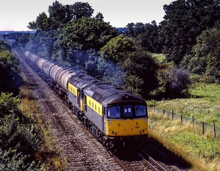 After running round at Alton, 33002 and 33025 head back to the Oil Terminal with 6Y50, the 09:16 Eastleigh East Yard - Holybourne empty tanks, on 10th August 1991. <br /> Scanned transparency.