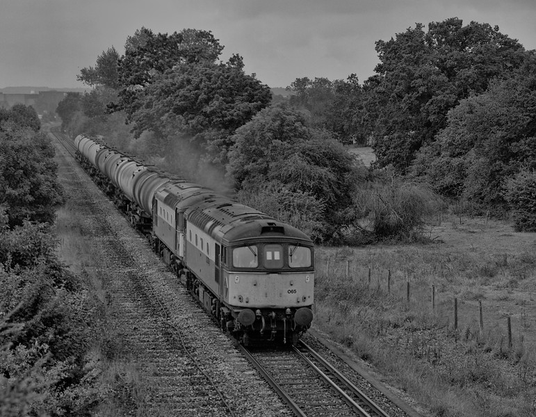 After running round at Alton, 33065 and 33057 head back to the Oil Terminal with 6Y50, the 09:16 Eastleigh East Yard - Holybourne empty tanks, on 14th September 1991.  <br /> Scanned negative.