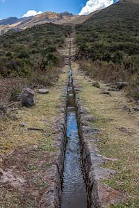 Ellenlange stenen geulen leiden naar een beschermd dal.