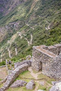 Op de achtergrond de vele haarspeldbochten die de busjes nemen om Machu Picchu te bereiken.