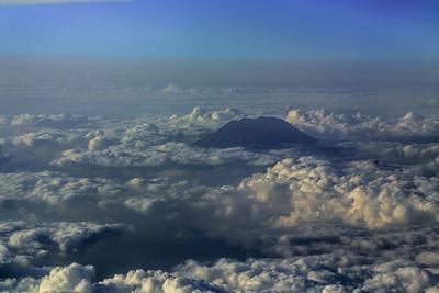 De vulkaan Agung komt piepen door de wolken bij de aankomst op Bali. Met dank aan Lion Air voor de vuile ruiten.