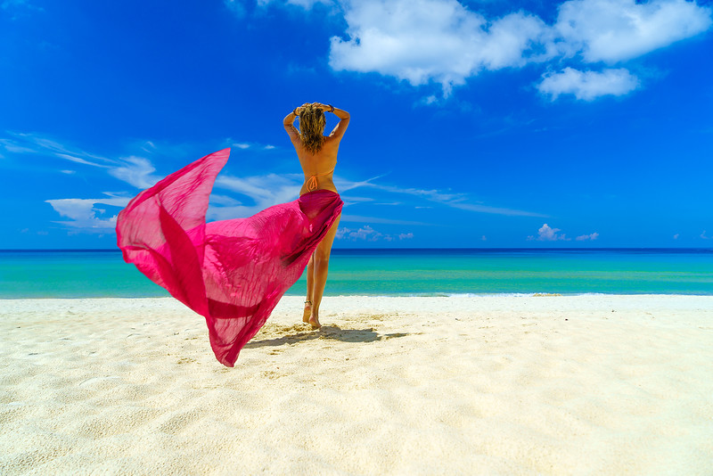 Woman with pink sarong on the tropical beach