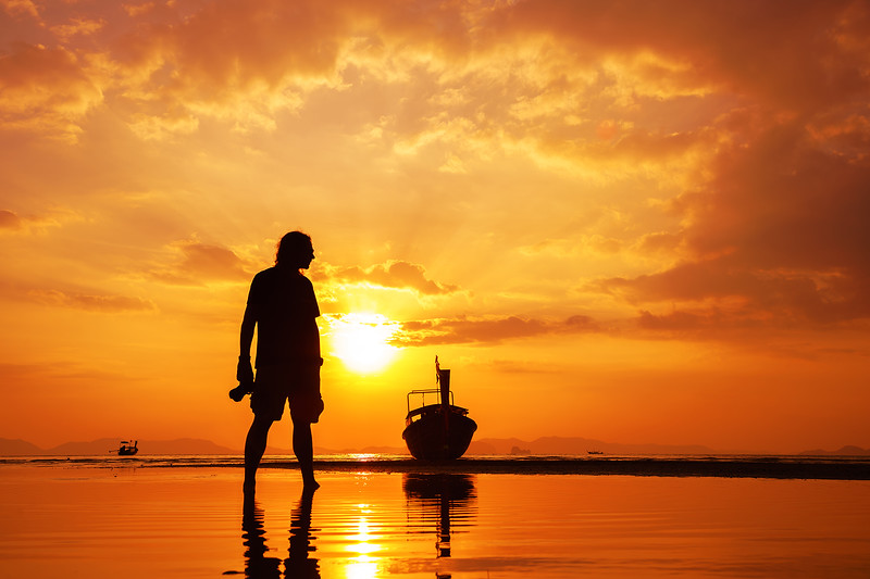 Silhouette of a photographer on beautiful tropical sunset