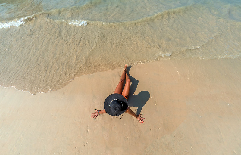 Top view of a woman at the tropical beach relaxing on the sand