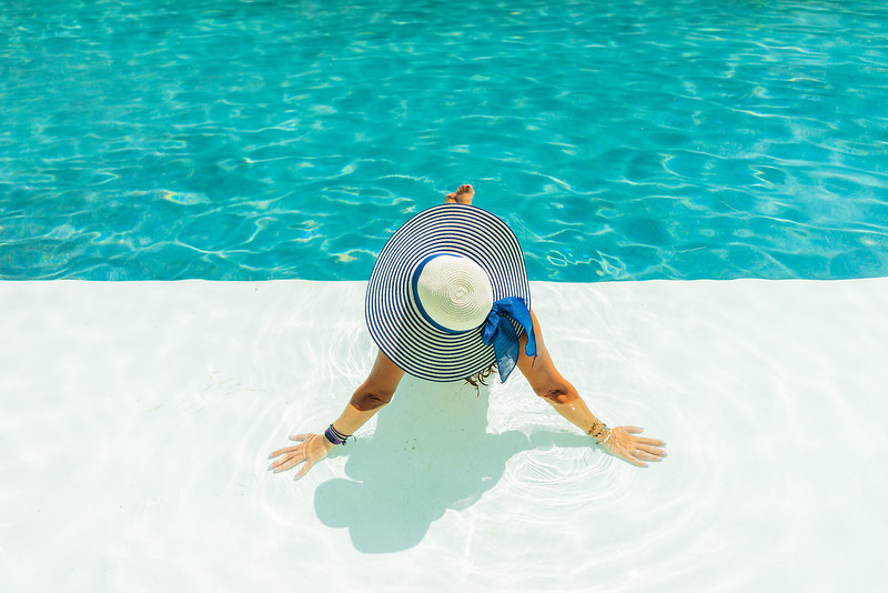 Woman relaxing in swimming pool at spa resort. r