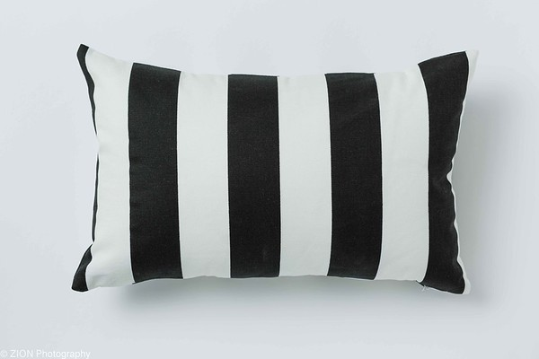 A Black and White Stripped Pillow on White