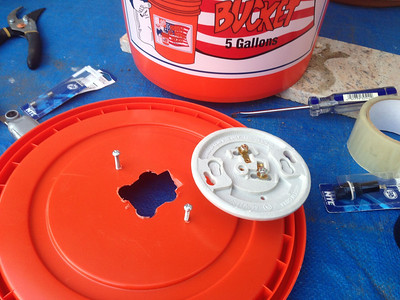 Step 3: Measure and cut a hole in the center of the bucket cover, so that you can wire the ceramic bulb holder through it.  Drill two small holes to the sides of the big hole, so that the bulb holder can be fastened with screws.  Make sure that the electric terminals not touch the junction box in any way.  Keep in mind that the CFL lamp would be placed inside the bucket, upside down.
