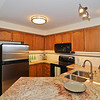 Open concept kitchen with stainless steel fridge, granite, sink, tile backsplash, and upgraded appliances.