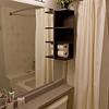 Master bathroom updated. Grey paint, new light fixture (Union Lighting), curved shower rod (Moen), and small matching wall shelves (Ikea Lillangen)