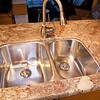 Undermount sink and pull-out faucet installed. Must wait at least 24 hours for the sink epoxy to set before hooking up the plumbing, though. Sink model is Kindred Canada KSDC8RU. Faucet and soap dispenser are Moen CA87006CSL.