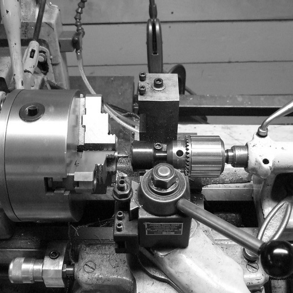 A wider shot showing how we use the die on the lathe.  It is mounted in a die holder, which is then mounted in the tailstock.  I manually advance the tailstock as the lathe turns the fastener.
