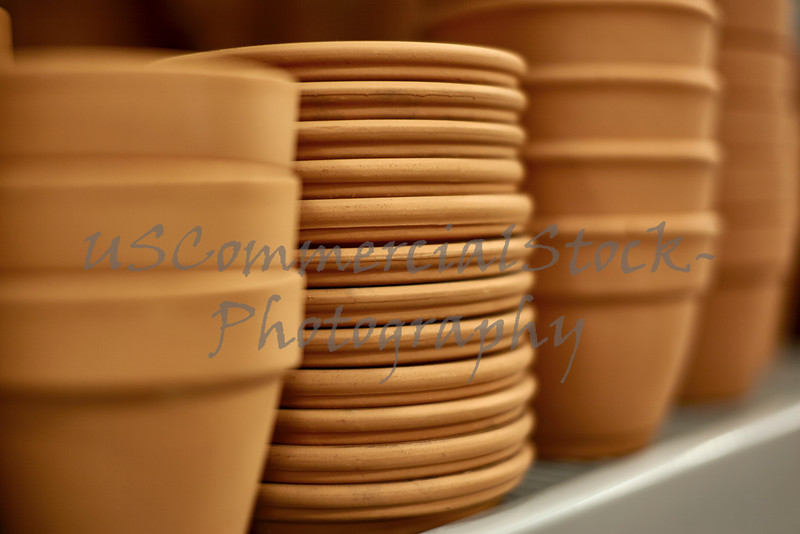 Rows of Clay Pots with Trays on Shelf