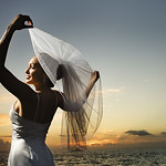 Bride holding out veil on beach.