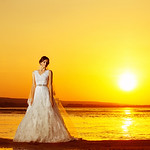 Beautiful bride in long white wedding dress standing at sea