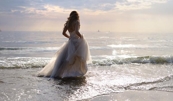 Bride walking along sea coast