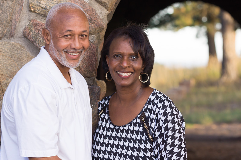 Portrait of a smiling man and woman, a married couple, in front of a stone wall and picturesque archway.