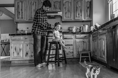 A father braids his young daughter's hair as she sits on a stool in their kitchen.