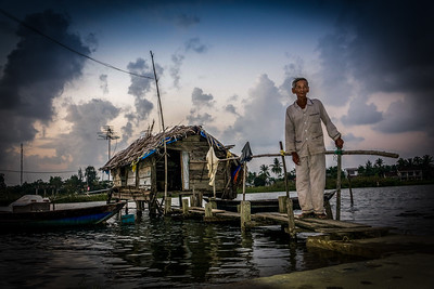 Vietnamese fisherman stands by his fishing boat and hut on An Hoi Island, Vietnam.   2017