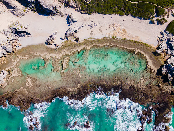 Aerial view of remote Overberg tidal pool and man walking, South Africa