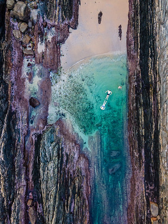 Aerial view of Otter Trail three hikers swimming in tidal pool, South Africa
