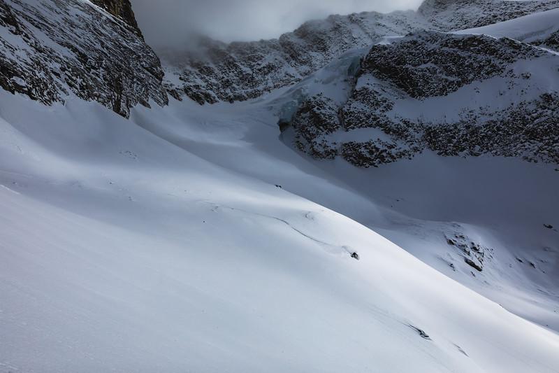 Matt Sterbenz skiing underneath pocket glaciers on Rodgers Pass. Checkerspot Road Trip.
