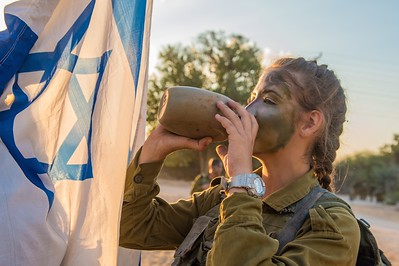 IDF soldier from the co-ed Combat Search and Rescue Battalion stops to drink some water during her Beret March in southern Israel.