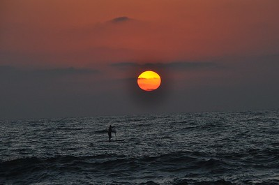 Man standing on a paddle board glides across the Mediterranean Sea off the coast of Tel Aviv, Israel at Sunset.